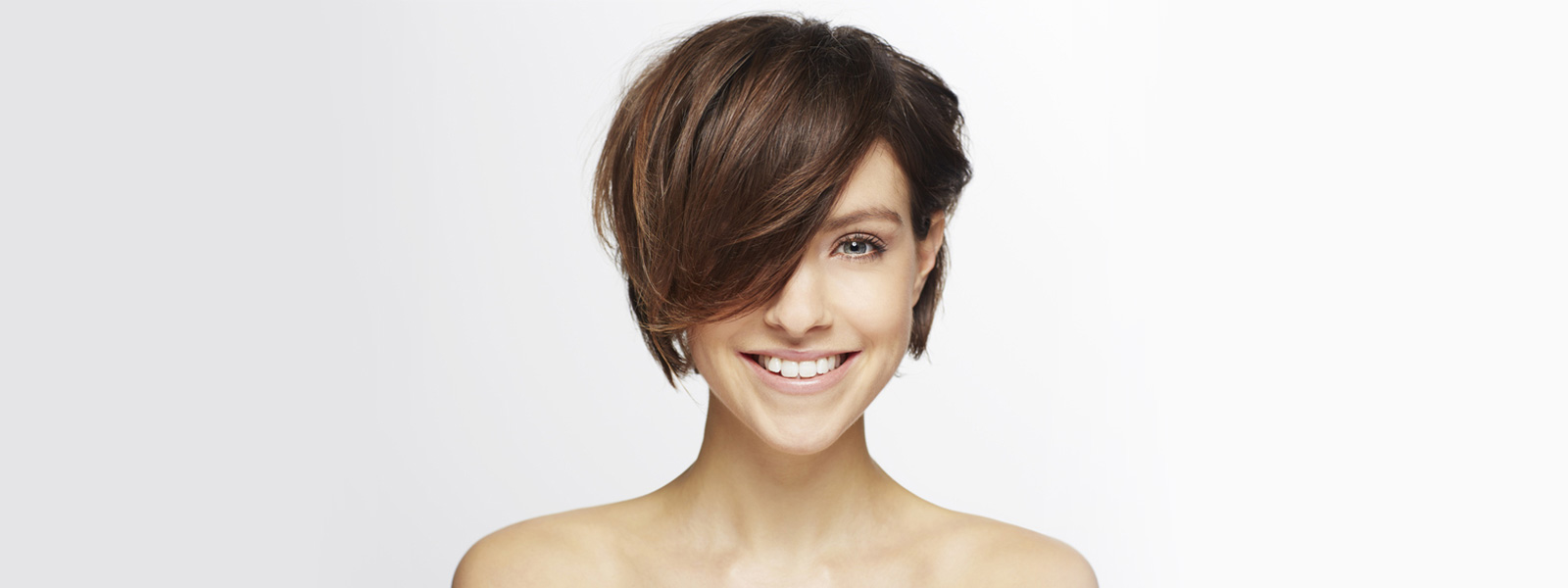 woman with short brown hair over her face smiling