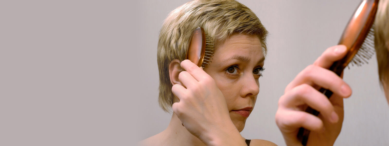 short haired woman brushing out thinning hair