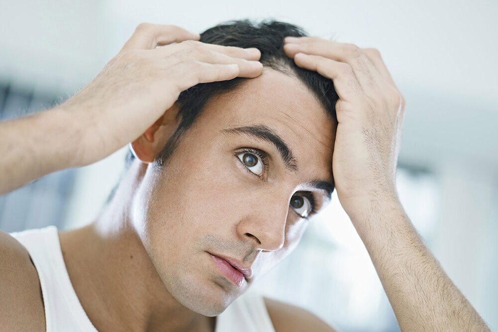 man with hands on his hair trying to understand hair loss