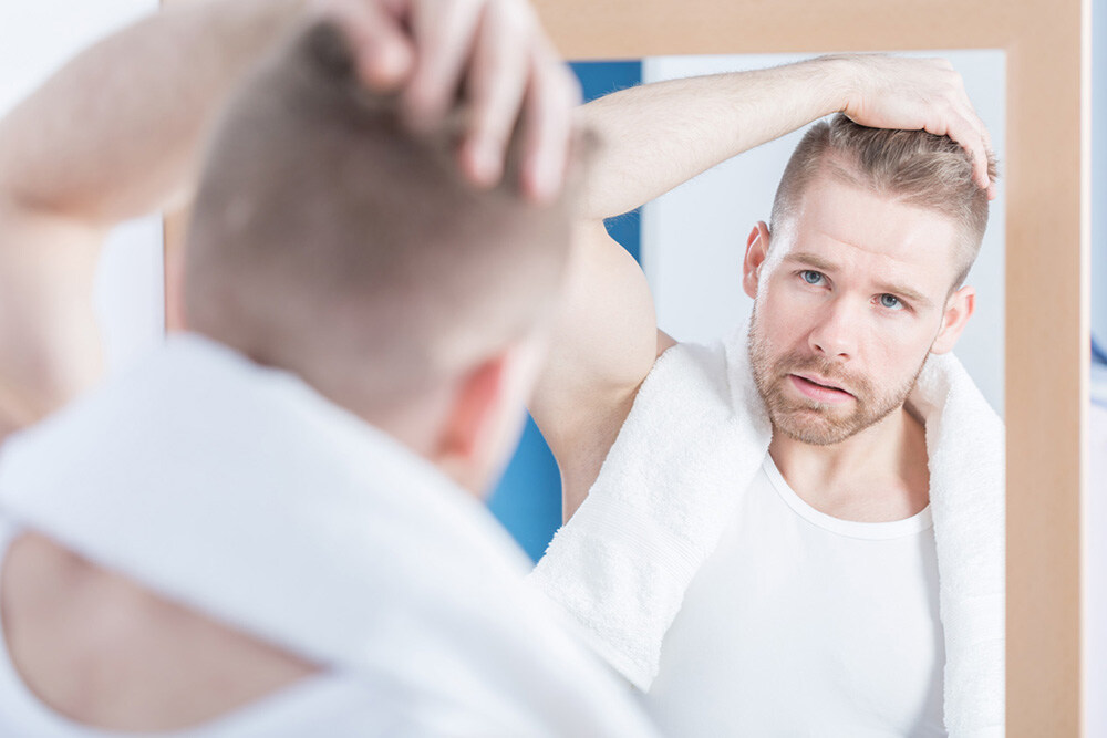 man applying ROGAINE® hair growth treatment