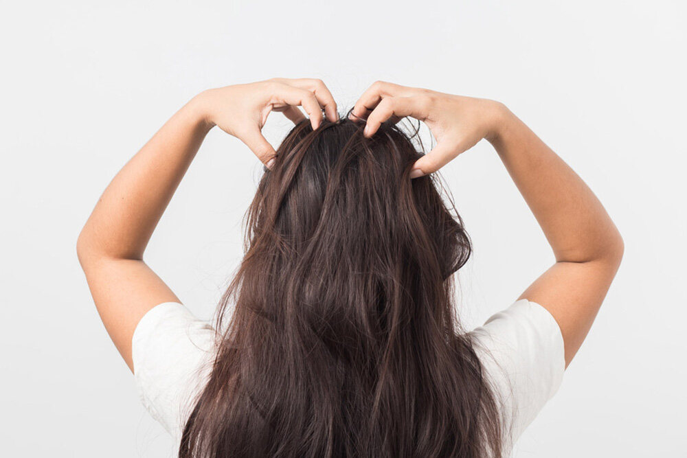 brunette woman massaging her scalp for hair growth