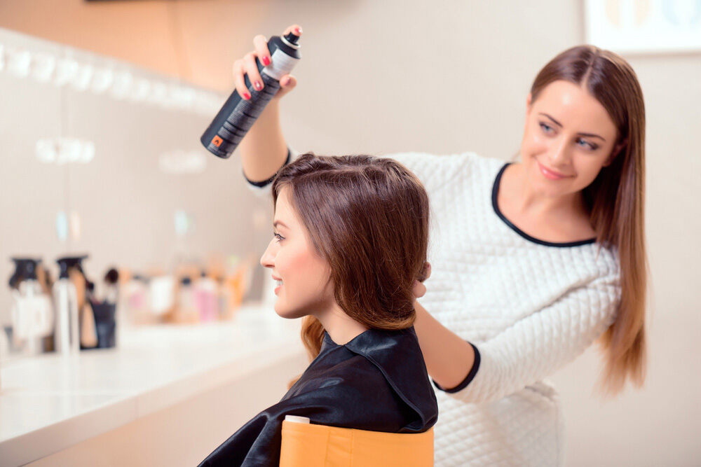 female hair stylist spraying clients hair with hair spray