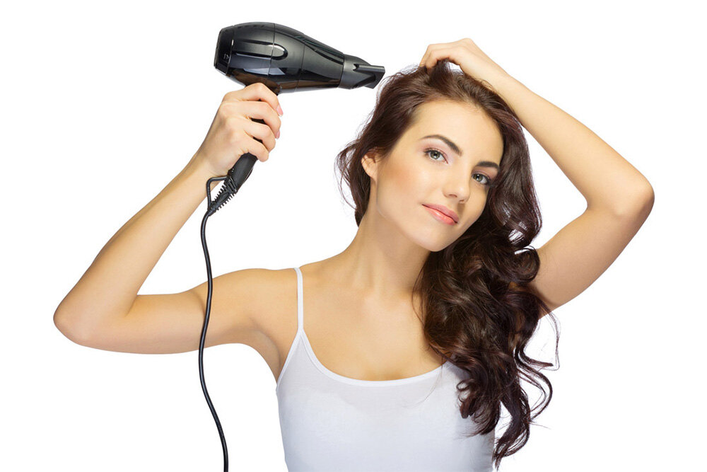 brunette woman using a hair dryer