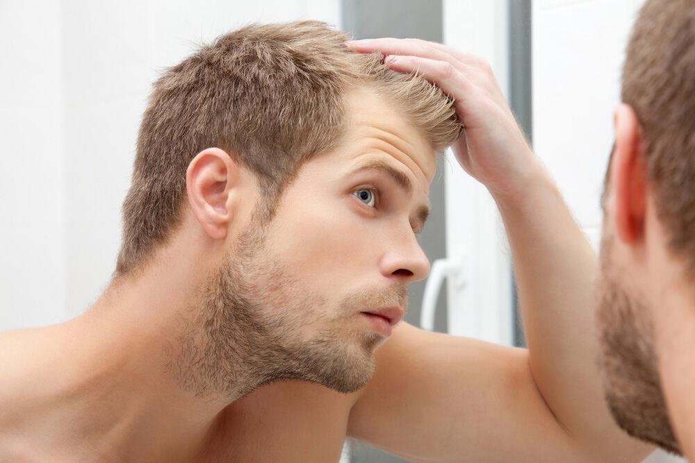 young man looking at his hair line in the mirror