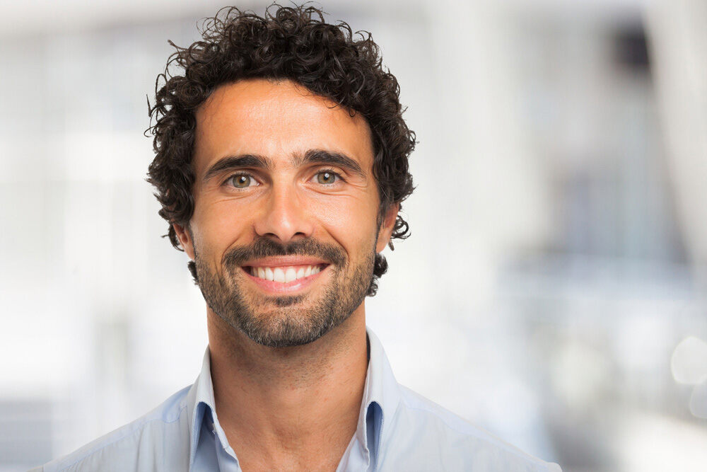 man with curly hair smiling