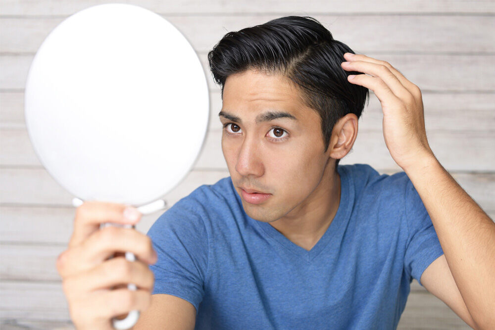 men with a handheld mirror looking at his hair