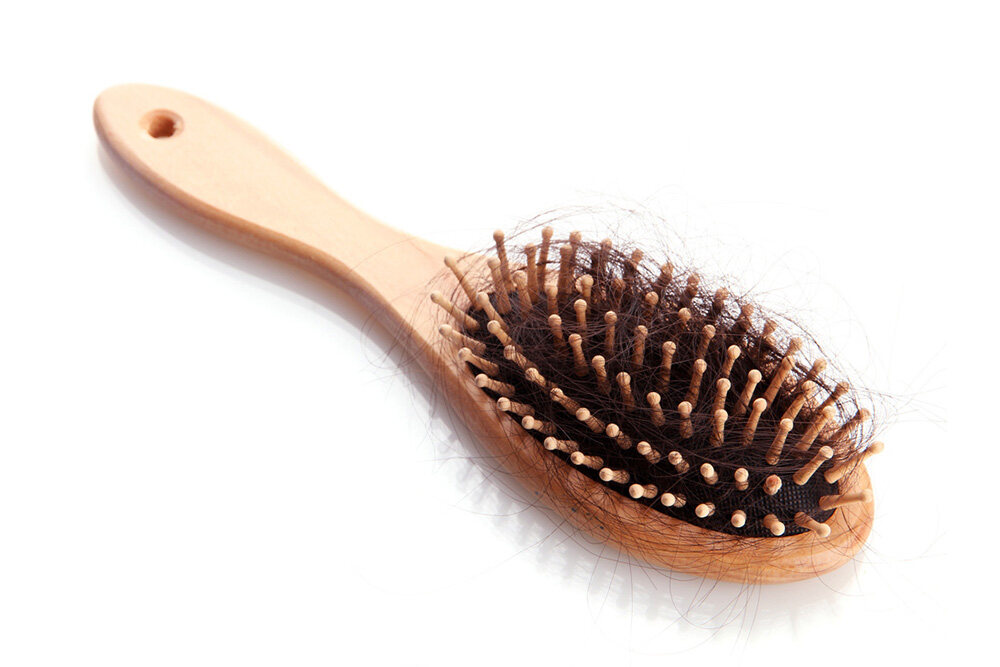 wooden hair brush with hair stuck inside