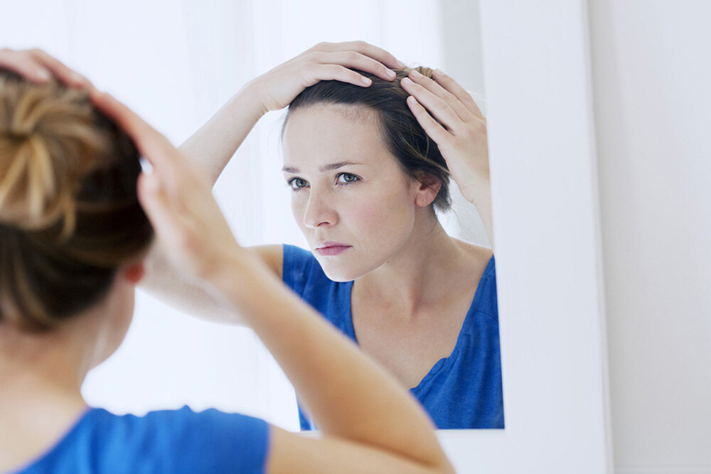 woman looking in the mirror trying to find out the root cause of hair loss