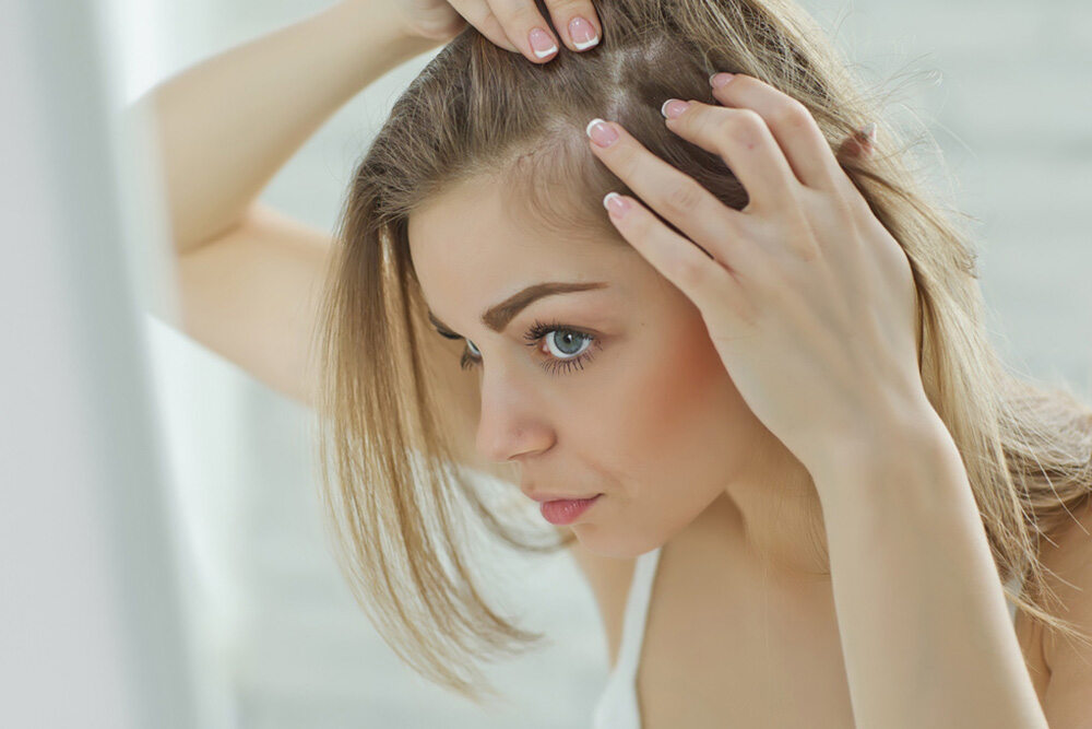 woman taking a closer look at her thinning hair in the mirror
