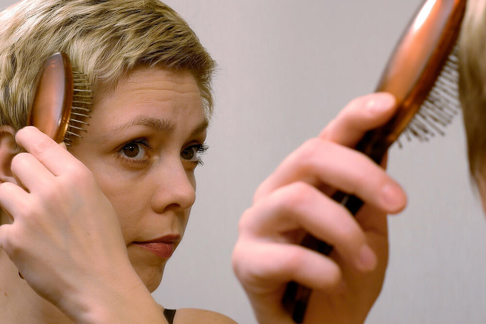 blonde woman brushing her short hair